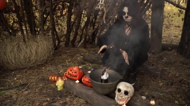 Hexe mit Skelett-Make-up zaubert im Wald