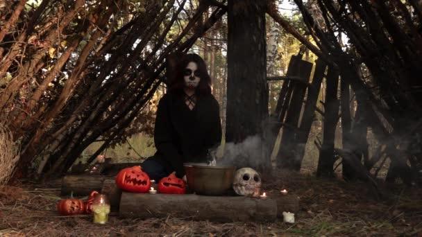 Hexe blickt in Zeitlupe in die Kamera, während sie an einem rituellen Tisch in der Natur sitzt