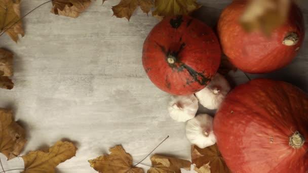 Horní pohled na suché javorové listí padající na stůl s dýněmi ve zpomaleném filmu