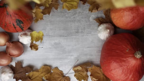 Maple leaves are falling down in the middle of wooden table with pumpkins at it