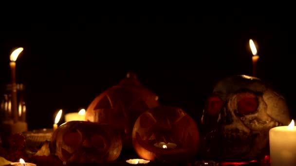 Klasická halloweenská výzdoba dýní se svíčkami a lebkovou kamerou sestupuje shora dolů