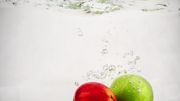 Zpomalit video různých jablek padající do vody s bublinami. Ovoce na izolovaném pozadí.