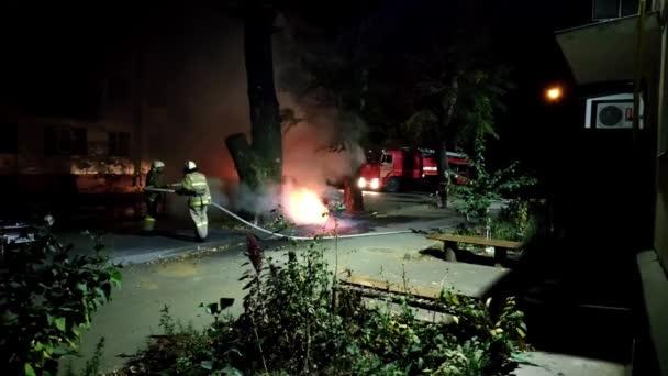 Feuerwehrleute löschen Auto, das von Vandalen gestellt wurde, aus dem es in einem Wohngebiet starken Rauch gibt