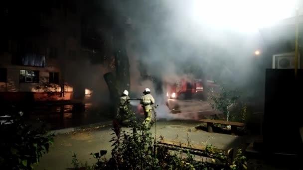 Zwei Feuerwehrleute versuchen in der Nacht ein brennendes Auto in einem Wohngebiet zu löschen