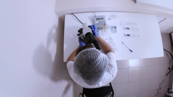 Woman laboratory worker is engaged in study of biological samples through a microscope