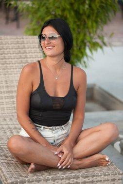 Beautiful black haired woman near pool in swimwear