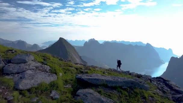 Dívka s batohem se tyčí na horském hřebeni