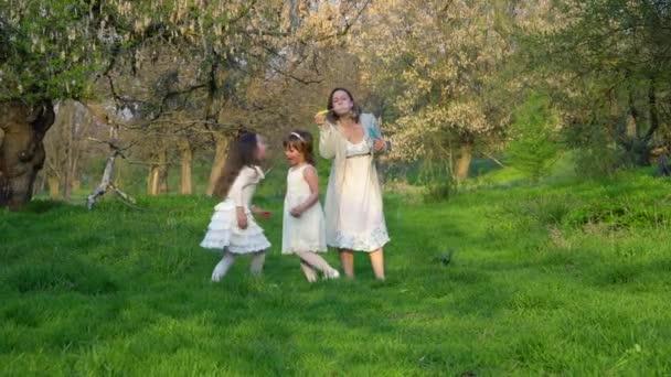 Šťastná mladá matka si zahrává s dcerami v parku