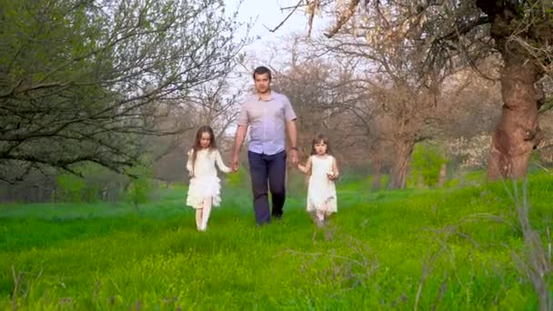 Father and daughters walk in the park
