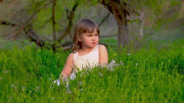 Dívka seděla na trávě a jedla jablko