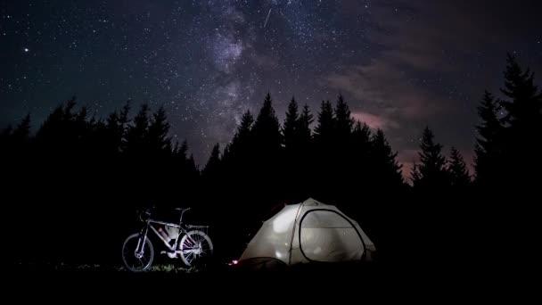 Egy férfi sziluettje egy sátorban éjszaka.