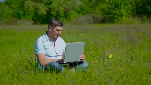 Üzletember Laptop mögött dolgozik Ül a füvön