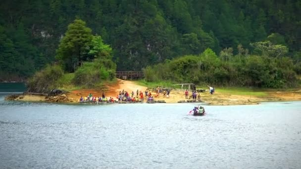 CHIAPAS, MEXICO-CIRCA AUGUST 2018: Tourists in log boats arrive to an island in the middle of a lagoon in the national park Montebello Lagoons.