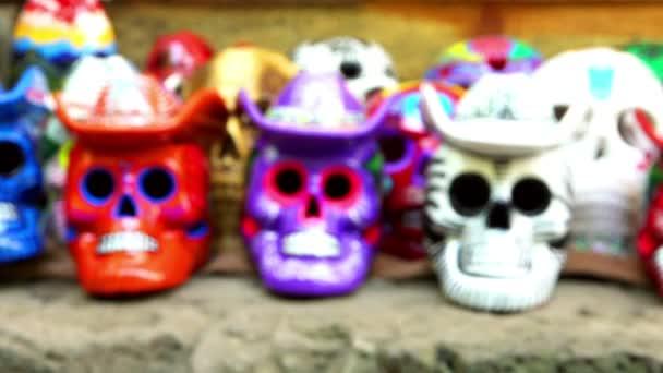 Bunte Schädel mit hüten, in einen Handwerkermarkt in Tepoztlan Mexiko angeboten.