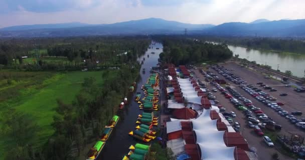 People enjoying a trip on a Trajinera (raft) in the canals of Xochimilco lake. Aerial view of the pier Cuemanco, many rafts anchored to the shore. This lake is an  attractive touristic of Mexico.TAKE3
