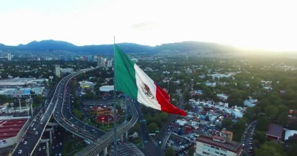 Letecký pohled na obrovské Mexická vlajka mávala, vzadu zářící slunce se schovává za horami. Take 2