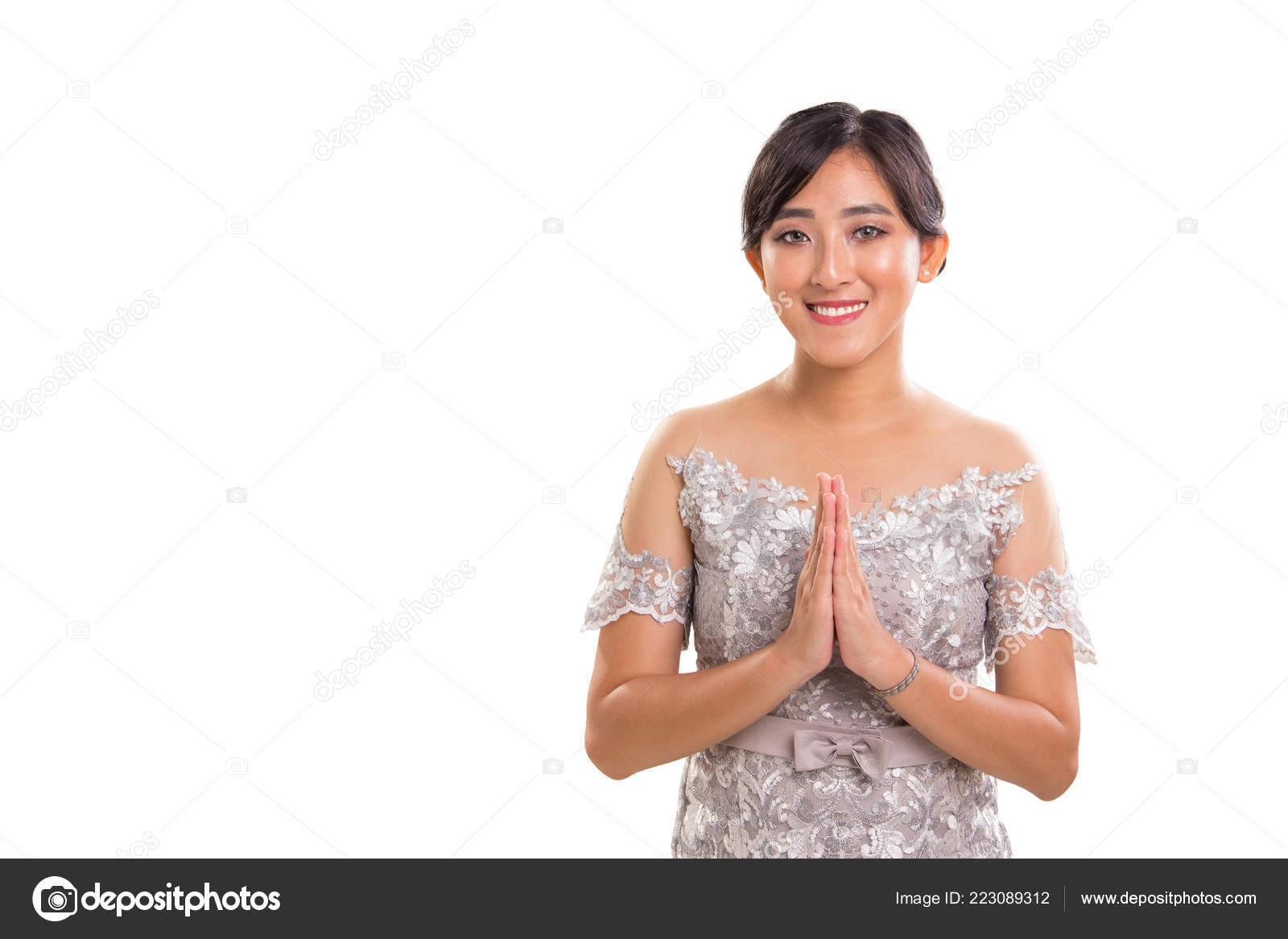 3df585a99 Warm greeting of young attractive female model of Southeast Asia ethnicity  wearing traditional formal attire posing with both palms clapping, ...