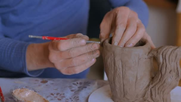 Profesionální potter, takže vzor na hlíny hrnek se speciálním nástrojem v dílně