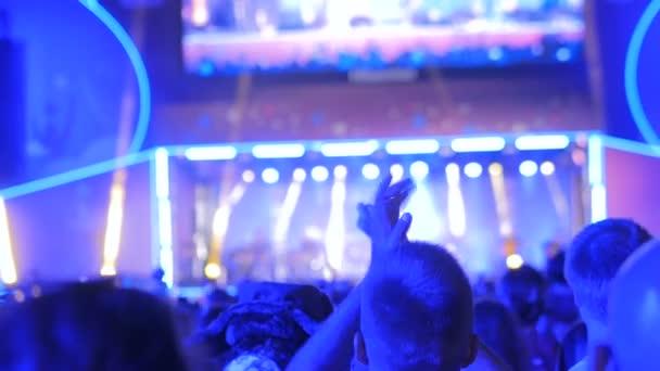 Emberek sziluettje bulizás és taps az éjszaka rock zene koncertet a színpad előtt