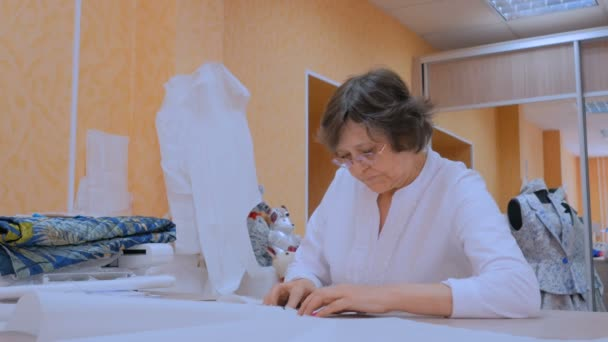Tailor working with pattern of new couture collection