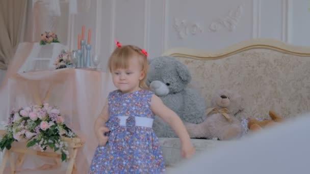Portrét legrační holčičky s medvědí panenkou doma