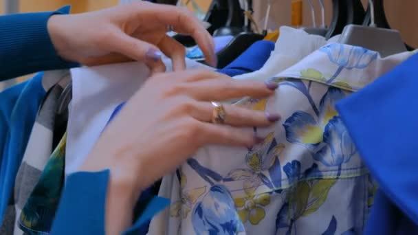 Detailní záběr záběr - žena ruce vyřadí závěs s barevné oblečení v butiku, předváděcí místnosti. Móda, konzumu a prodej koncepce