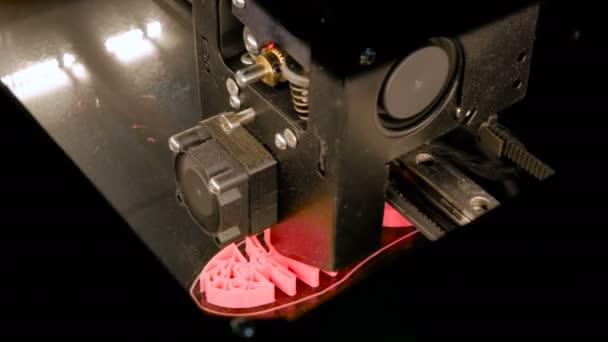 Modern 3D printer machine printing plastic model of pink fish skeleton