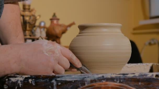 Professionelle Töpfer Gestaltung Topf mit Spezialwerkzeug in Keramikwerkstatt