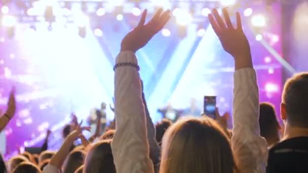 Emberek sziluettje szórakozóhely, éjszakai szabadtéri koncerten a színpad előtt