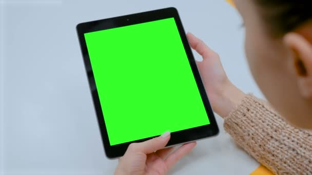 Woman touching green screen touchscreen display of black digital tablet at home