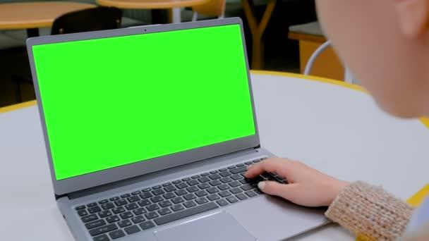 Frau blickt in Café auf Laptop mit leerem grünen Bildschirm