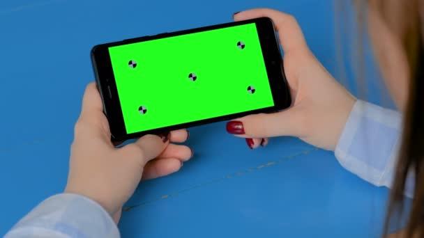 Frau blickt auf schwarzes Smartphone mit leerem grünen Bildschirm - chroma key concept