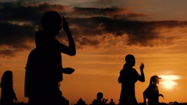 Az emberek táncolnak napnyugtakor