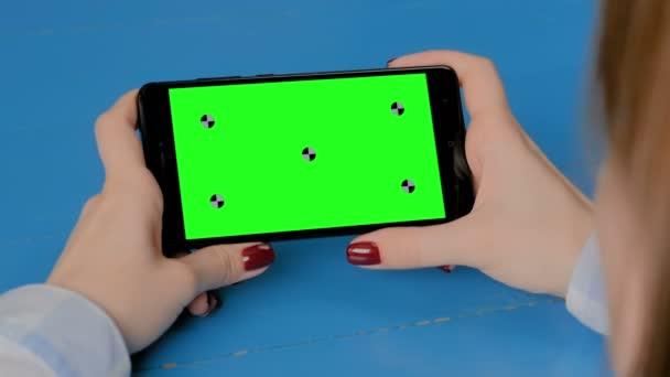 Nő nézi a fekete okostelefon üres zöld képernyő - chroma kulcs koncepció