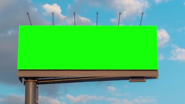 Timelapse - prázdný zelený billboard a pohybující se bílé mraky proti modré obloze