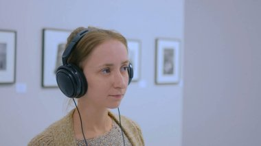 Woman looking at exposition, using headphones and listening audio guide