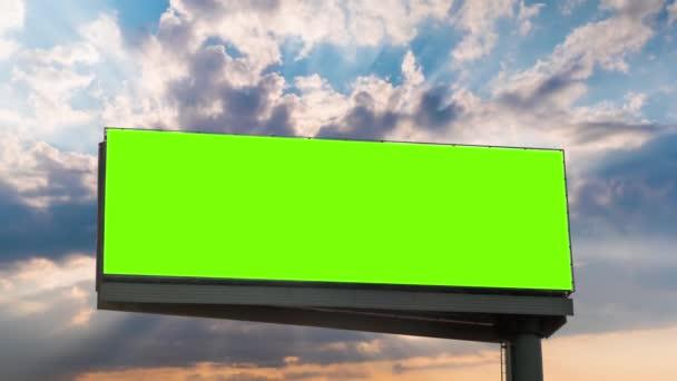 Timelapse - prázdný zelený billboard a sluneční paprsky zářící mraky při západu slunce