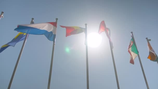 Super slow motion - colorful flags fluttering in the wind - diplomacy concept