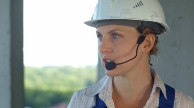 Female builder engineer is considering a plan for new construction and talking via microphone