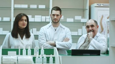 Positive team of pharmacists looking at camera at the hospital pharmacy