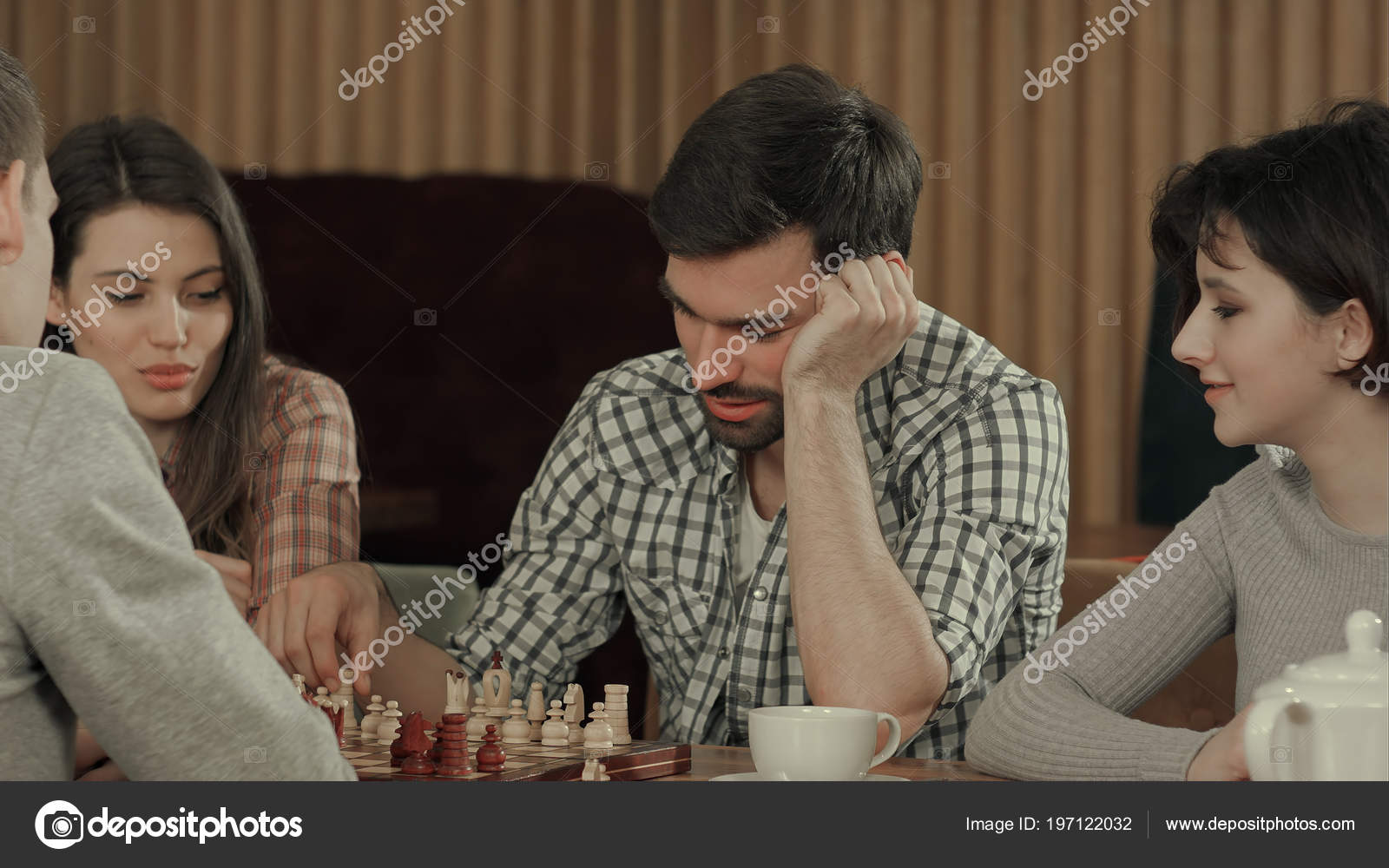 Young men playing chess with friends — Stock Photo