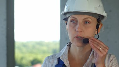 Builder supervisor oversees building site and gives instructions to workers over the intercom