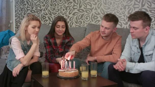 Dospívající chlapec osvětlení narozeninové svíčky na dort s přáteli doma