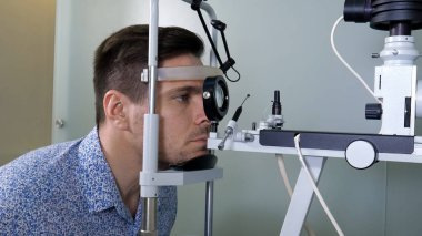 Man in optometrists office checking her vision