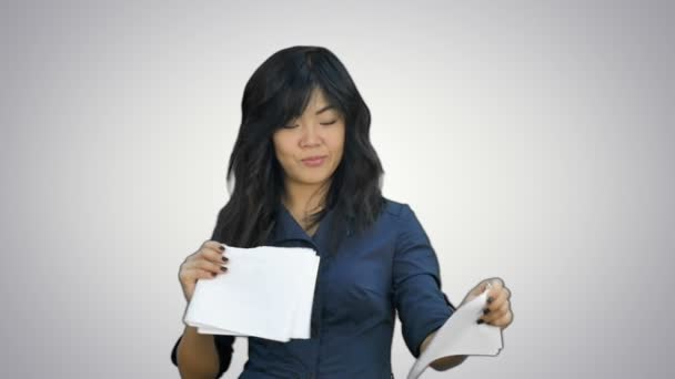 Confident asian businesswoman tearing the paper into small pieces and throwing it on white background