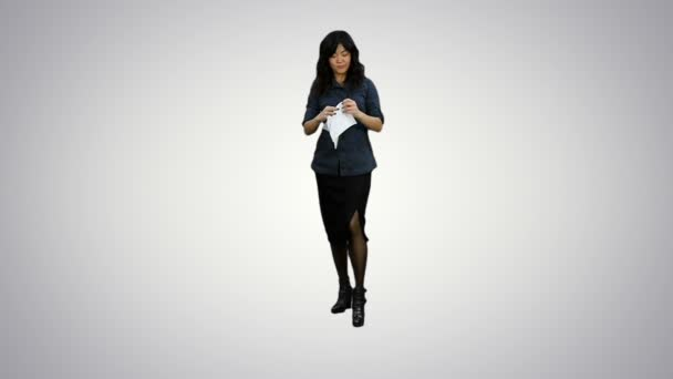 Angry young businesswoman tearing paper on white background