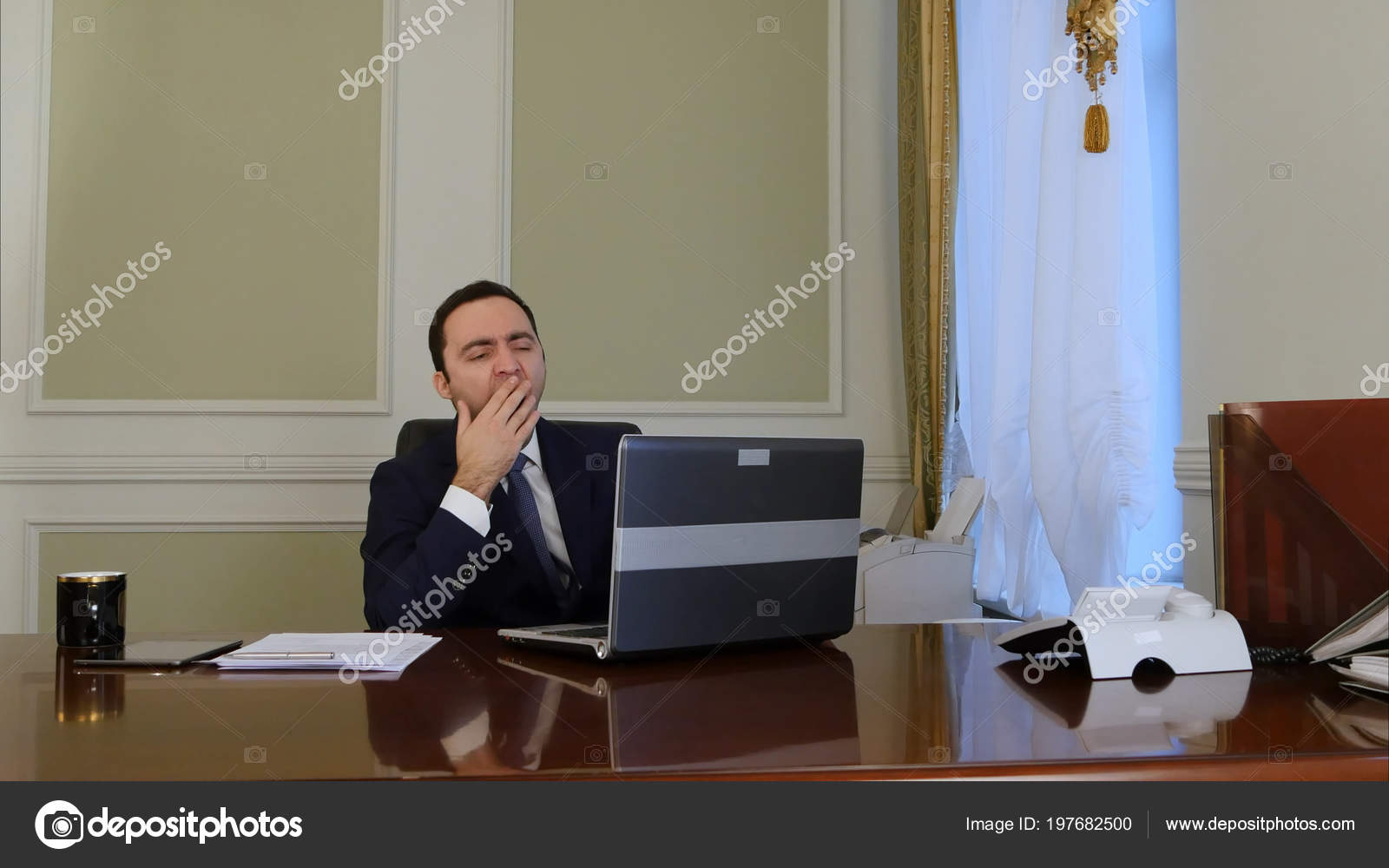 Tired businessman finishes working on laptop, relaxing and