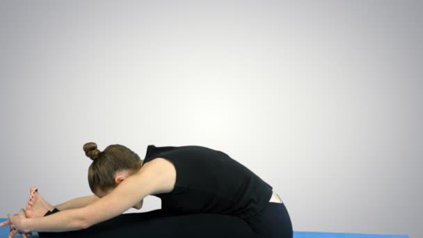 Mladá žena strečink nohou na podložku, cvičí jógu na bílém pozadí