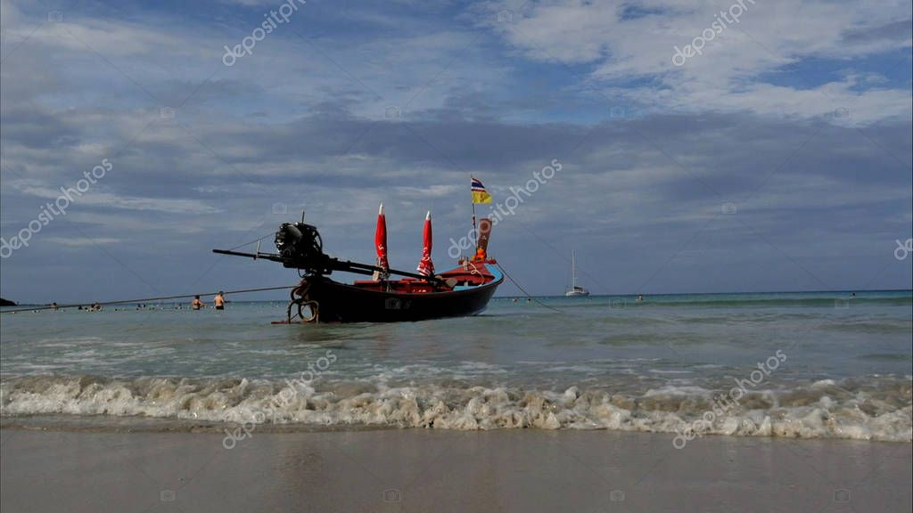 Thai traditional wooden boat with ribbon decoration at ocean shore under blue sky