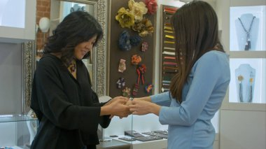 Two young women try on a desined jewellery in a store